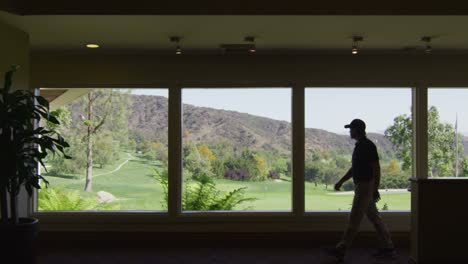 A-golfer-inside-a-country-club-with-a-golf-course-visible-through-the-windows