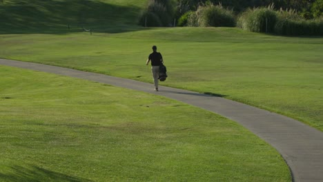 A-golfer-walks-along-a-path-on-a-golf-course