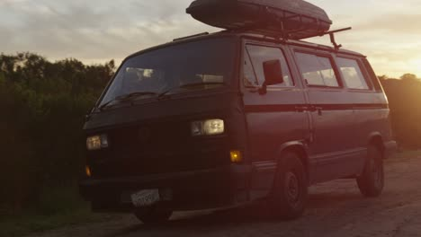 A-surfer-pulls-up-in-a-camper-van-with-a-board-on-top-at-daybreak-on-a-dirt-road-in-a-coastal-area
