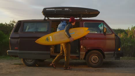 A-suffer-gets-his-gear-out-of-his-camper-van-and-prepares-to-hike-out-to-the-surf-in-a-coastal-area