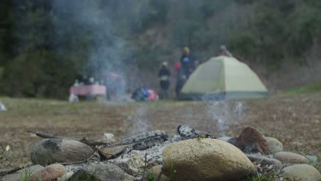 An-extinguished-campfire-smolders-while-campers-move-in-the-background-near-a-tent