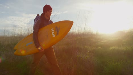 A-surfer-carries-his-board-as-he-hikes-down-to-a-remote-surf-spot-in-a-coastal-area-2
