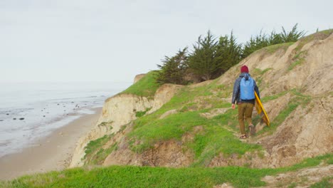 A-surfer-runs-for-the-beach-following-a-long-hike-to-a-remote-surf-spot