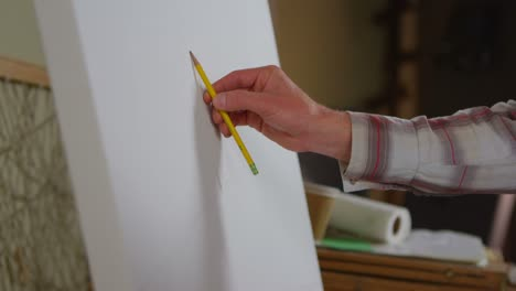 Closeup-of-a-hand-as-an-artist-begins-to-sketch-on-a-blank-canvas