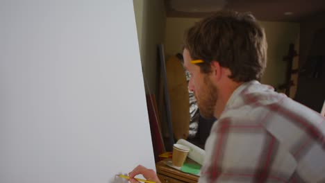 Over-the-shoulder-view-of-an-artist-sketching-on-a-blank-canvas