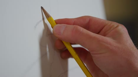 Closeup-of-a-hand-as-an-artist-begins-to-sketch-on-a-blank-canvas-1