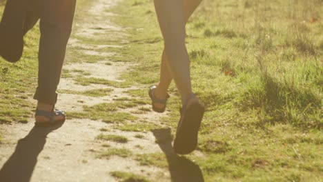 Closeup-of-a-couple-s-feet-as-they-run-on-a-path-towards-a-forest