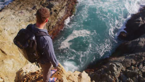 High-angle-view-of-a-man-looking-down-at-the-ocean-from-the-edge-of-a-sea-cliff