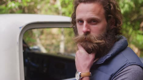 A-man-gazes-at-the-camera-and-thoughtfully-strokes-his-beard