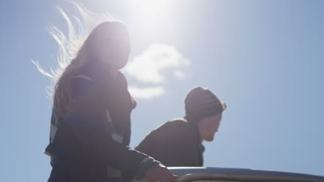 A-couple-stands-in-the-bed-of-a-pickup-truck-as-it-drives-along-a-rural-road-1