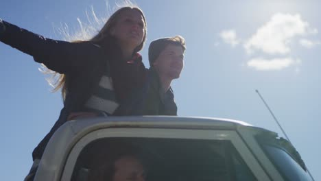 A-couple-stands-in-the-bed-of-a-pickup-truck-as-it-drives-along-a-rural-road-2
