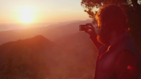 A-man-takes-a-picture-of-the-sunset-at-a-campsite