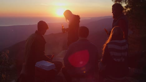 A-group-of-friends-drink-beer-at-a-campsite-as-the-sun-sets