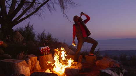 A-man-sprays-lighter-fluid-on-a-campfire-while-drinking-beer-at-a-campsite