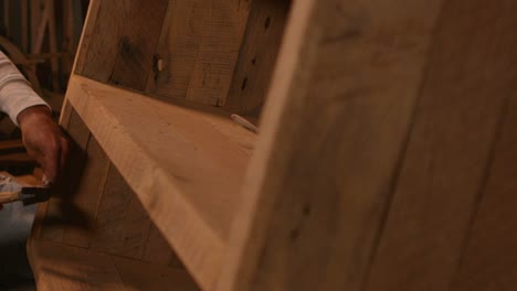 The-camera-pans-left-to-reveal-a-woodworker-hammering-a-nail-into-a-bookshelf