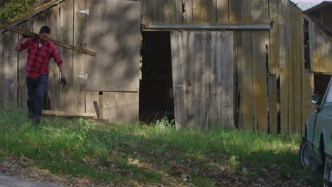 A-man-carries-a-board-to-a-pickup-truck-parked-outside-an-old-barn-1