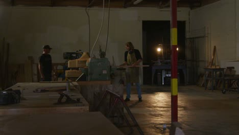 A-woodworker-places-a-plank-on-a-workbench-while-a-forklift-maneuvers-in-the-background