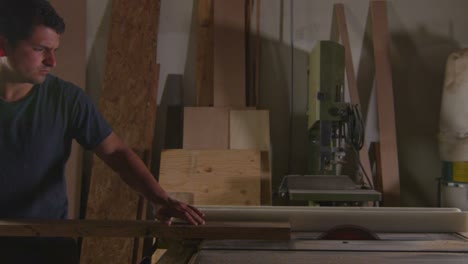 A-woodworker-saws-a-plank-on-a-workbench