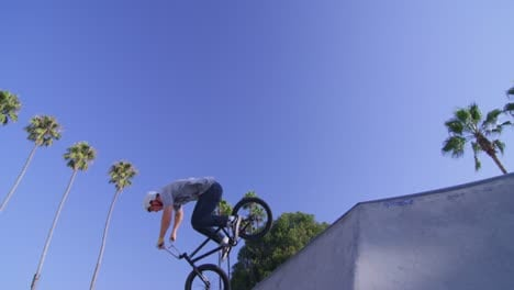 Low-angle-view-of-a-BMX-bike-rider-executing-a-jump-at-a-skatepark-1