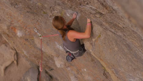 High-angle-view-looking-straight-down-at-a-rock-climber-scaling-a-sheer-rock-wall