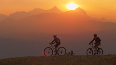 Two-mountain-bikers-pull-to-a-stop-on-a-hillside-at-sunset
