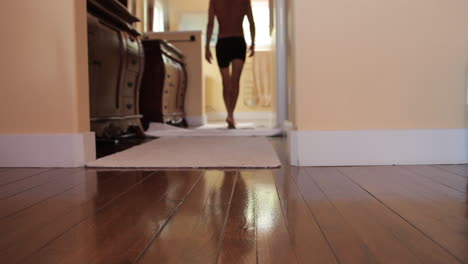 A-man-clad-only-in-his-underwear-walks-across-a-wooden-floor-and-into-the-dressing-room