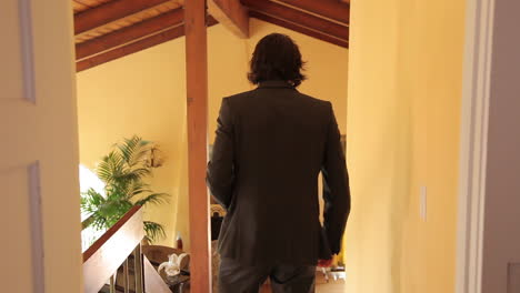 A-man-well-dressed-walks-down-a-corridor-in-his-house-and-performs-a-spin-move