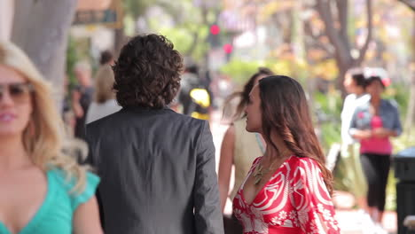 Women-stop-and-look-at-a-well-dressed-man-walking-down-the-street-One-woman-gets-a-text-from-him