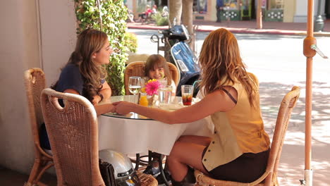 Two-women-friends-talk-at-an-outdoor-cafe-with-their-children-at-the-table-The-woman-gets-up-and-leaves-on-her-Vespa-scooter