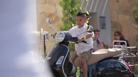 A-young-boy-is-delighted-to-sit-on-a-Vespa-motorscooter