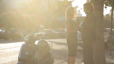 A-man-runs-down-the-street-and-greets-a-woman-getting-onto-her-Vespa-motorbike