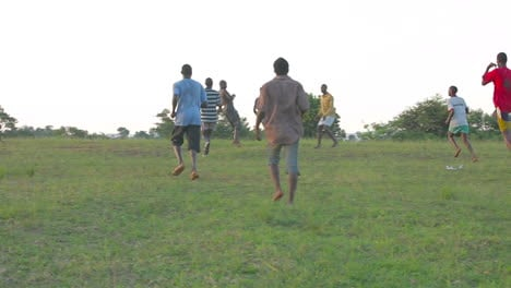 African-children-play-soccer-on-a-grassy-field