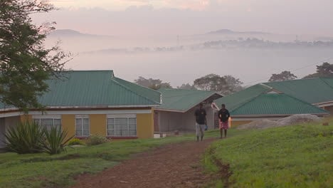 Two-Africans-walk-near-a-compound-of-buildings-makes-for-a-retreat-in-Uganda-Africa