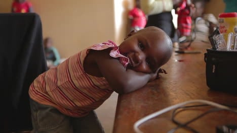 A-cute-African-girl-puts-her-head-on-a-table-and-flirts-with-the-camera