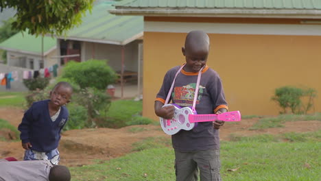 An-african-boy-plays-a-pink-guitar-in-Uganda