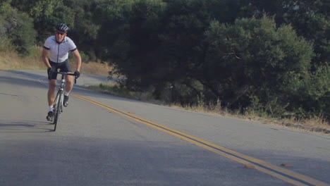 Traveling-slow-motion-shot-of-mountain-bike-rider-pedaling-uphill-along-a-highway