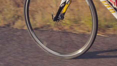 Traveling-slow-motion-shot-of-mountain-bike-wheels-moving-a-long-a-paved-road