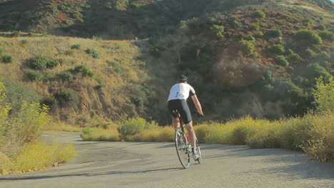 Slow-motion-shot-of-man-pedaling-mountain-bike-uphill-on-a-two-lane-paved-road-2
