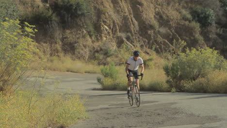 Slow-motion-shot-of-man-pedaling-mountain-bike-uphill-on-a-two-lane-paved-road-4