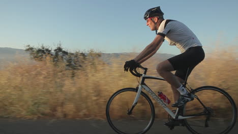 Slow-motion-traveling-shot-of-a-man-coasting-downhill-on-a-mountain-bike