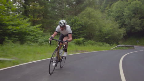 Traveling-shot-as-a-mountain-biker-moves-fast-along-a-two-lane-highway-on-a-cloudy-day