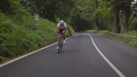 Traveling-shot-as-a-mountain-biker-moves-fast-along-a-two-lane-highway-through-a-forest-region-4