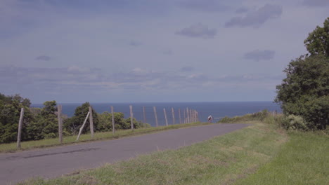 A-mountain-biker-moves-fast-on-a-two-lane-highway-along-a-coastline-1