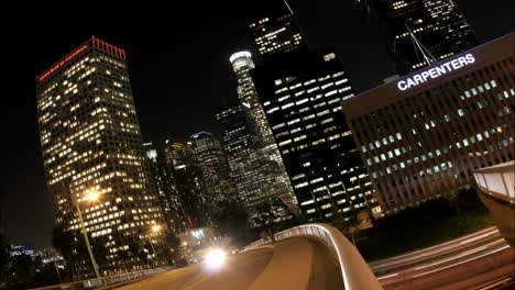 Timelapse-of-Los-Angeles-city-traffic-with-illuminated-skyscrapers-towering-behind