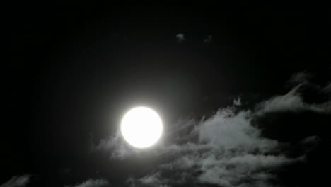 A-bright-full-moon-rises-above-swiftly-moving-clouds-in-the-night-sky