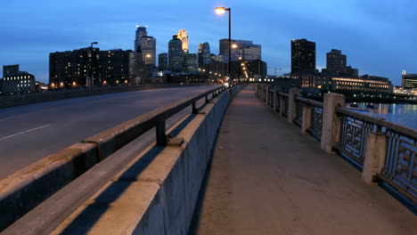 Pedestrians-and-vehicles-cross-a-bridge-in-downtown-Minneapolis-as-the-evening-sky-darkens-to-night
