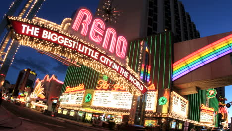 Tilt-shot-of-accelerated-traffic-passing-under-a-welcome-sign-for-Reno-Nevada-the-Biggest-Little-City-in-the-World-̨-at-night