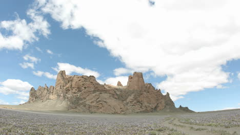 Sunlight-reflects-in-patches-as-fluffy-white-clouds-pass-over-New-Mexico\-s-Shiprock