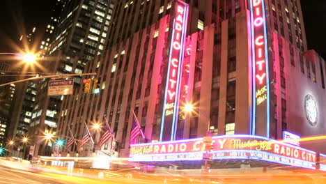 Slow-downward-pan-of-an-accelerated-shot-of-traffic-passing-in-front-of-Radio-City-Music-Hall-at-night