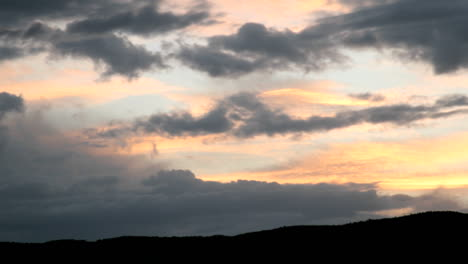A-gold-and-orange-sky-intensifies-in-color-as-it-is-obscured-beneath-dark-clouds